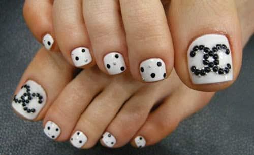 1) Diseño con apliques en las uñas de los pies donde observamos piedras de color blanco y negras