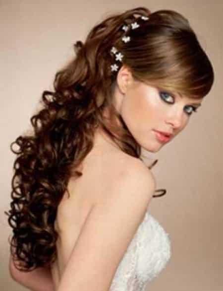 peinado recogido para cabello largo que le va por la espalda con bucles y con un detalle de flores tejidas para el pelo para verano de fiesta