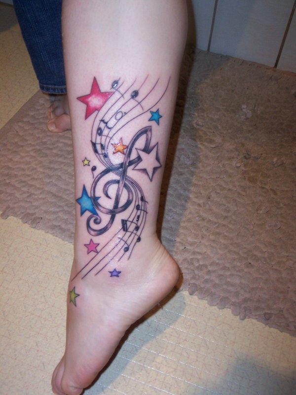 notas musicales en tatuaje a color en pierna