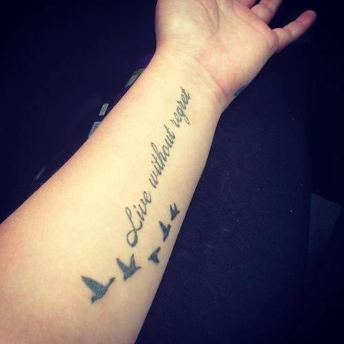 Tatuaje de frase de una linea en ingles con el detalle de aves volando en  ella para representar la libertad