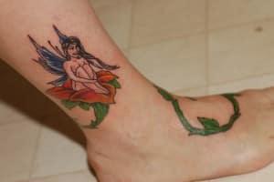 tatuaje a color en parte del pie con ramas verdes
